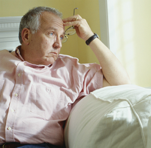 Man sitting on sofa in living room, looking out window.