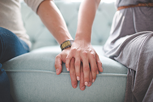 Two people holding hands while sitting on a couch
