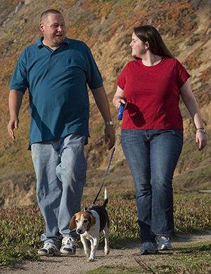 Man and woman walking with their dog.
