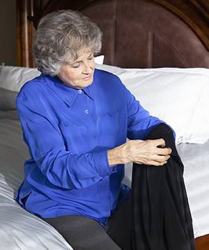 Woman sitting on bed, putting on jacket.