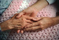 Picture of elderly woman and younger woman holding hands