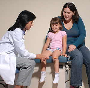Healthcare provider using reflex mallet on girl's knee while woman looks on.
